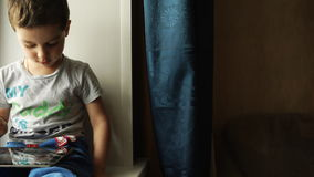 Child sits on a windowsill and uses a tablet pc stock video