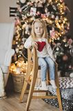 Portrait of a child on a background of Christmas tree decorated. The child sits on a wooden chair beside the Christmas tree Stock Photography