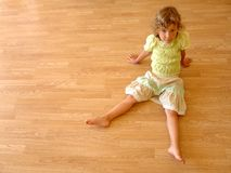 Child sits on wooden floor. Little girl sits on wooden floor Stock Photo