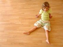 Child sits on wooden floor stock photo