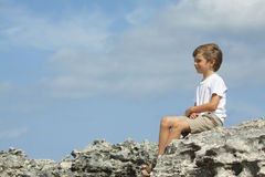 Child sitting. Boy sitting, on a nice summer day, by the seashore Stock Photos