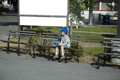 Child sitting. Young boy sitting alone in fron of empty billboard Royalty Free Stock Photo