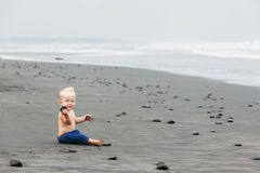 Child sitting alone on black sand sea beach. Portrait of smiling child sitting and playing alone with fun on balinese black sand sea beach before swimming Family Stock Photos