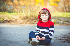 Child sitting on asphalt, in a red jacket with a hood. Royalty Free Stock Photography