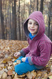 Child sitting in autumn or fall forest Stock Image