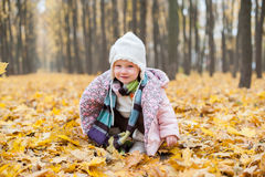 A child sitting in autumn leaves Stock Image