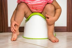 Child is sitting on baby potty stock photography