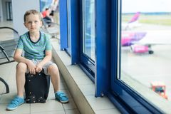 Child sitting at bag at the airport Stock Photo