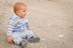 A child sitting on a beach. In autumn Royalty Free Stock Images