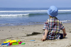 Child sitting on the beach and looking at the water Royalty Free Stock Photography
