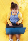 Child  sitting on a bean bag with laptop Royalty Free Stock Photo