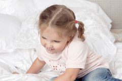 The child is sitting on the bed. Portrait of smiling girl with braids Stock Photo