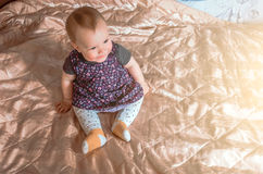 A child is sitting on the bed and smiling. stock photography
