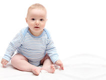 Child sitting on bed. Child sitting on white bed Stock Photo