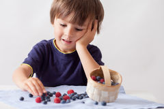 Child, sitting behind a table with raspberries and blueberries Stock Photography