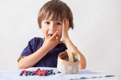 Child, sitting behind a table with raspberries and blueberries Royalty Free Stock Photography