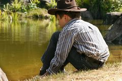 Child sitting by a billabong Royalty Free Stock Photos
