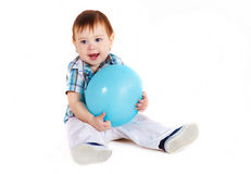 Child sitting with blue baloon. And hugs it Royalty Free Stock Photo