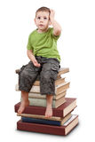 Child sitting on books. Child sitting on a stack of books and looking up royalty free stock images