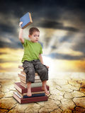 Child sitting on books. Child sitting on a stack of books and hold a book in hand, sunrise in background stock photo