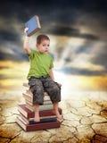 Child sitting on books Stock Photo