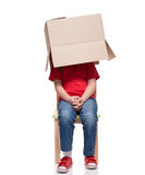 Child sitting on a chair with big box covered head Stock Images