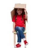 Child sitting on a chair with big box covered head. Isolated on white Stock Photography