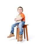 Child sitting on a chair with a book, on white background Royalty Free Stock Photography