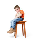 Child sitting on a chair with a book, on white background Royalty Free Stock Image