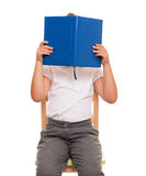 Child sitting on a chair covered face with blue book Royalty Free Stock Image
