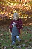 Child sitting on a chair in the park Stock Image