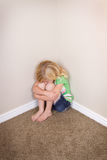 Child sitting in corner Stock Photo