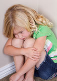 Child sitting in corner Royalty Free Stock Photography