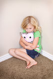 Child sitting in corner. Young child or preschooler sitting in corner, with a sad look on face, holding a stuffed animal for comfort stock photo