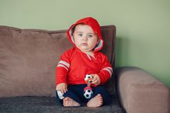Child sitting on couch and holding football soccer toy Stock Image