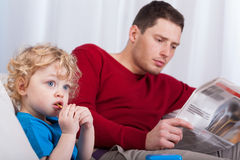 Child sitting with dad reading newspaper Stock Image