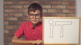 Child sitting at the desk holding flipchart with lettering it on the background red brick wall. stock video footage