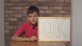 Child sitting at the desk holding flipchart with lettering ok on the background red brick wall. stock video