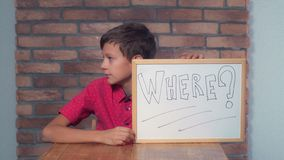 Portrait little boy showing whiteboard with handwriting word whe. Child sitting at the desk holding flipchart with lettering where on the background red brick stock photos