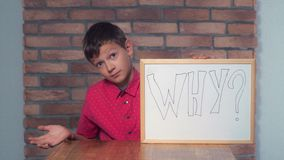 Child sitting at the desk holding flipchart with lettering why o. Portrait little boy showing whiteboard with handwriting word why. Schoolboy with asking on his stock photo