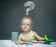 A child sitting at a desk with paper and colored pencils. A child in glasses sitting at a desk with paper and colored pencils Stock Photo