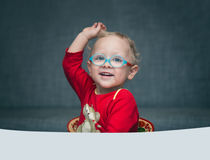 A child sitting at a desk with paper and colored pencils. A child in glasses sitting at a desk with paper and colored pencils Royalty Free Stock Image