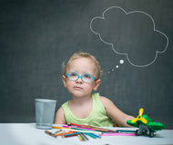 A child sitting at a desk with paper and colored pencils Stock Photos