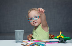 A child sitting at a desk with paper and colored pencils. A child in glasses sitting at a desk with paper and colored pencils Stock Image