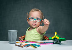 A child sitting at a desk with paper and colored pencils. A child in glasses sitting at a desk with paper and colored pencils Royalty Free Stock Images