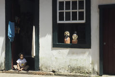 Child sitting at the door of his house in Tiradentes, Minas Gera Stock Photo