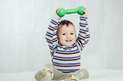 The child is sitting with dumbbells in hand. The child is involved in sports, fitness lifting dumbbell Royalty Free Stock Image