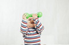 The child is sitting with dumbbells in hand. The child is involved in sports, fitness lifting dumbbell Stock Photography