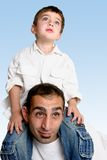 Child sitting on father's shoulders. Sky is the limit....   A child sits atop his father's shoulders looking skyward Stock Photos