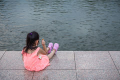 Child Sitting and Feeding Fish in Pond Stock Photos